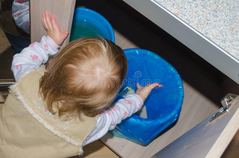 Em uma cubeta de limpar para fora a criança do lixo imagens de stock royalty free