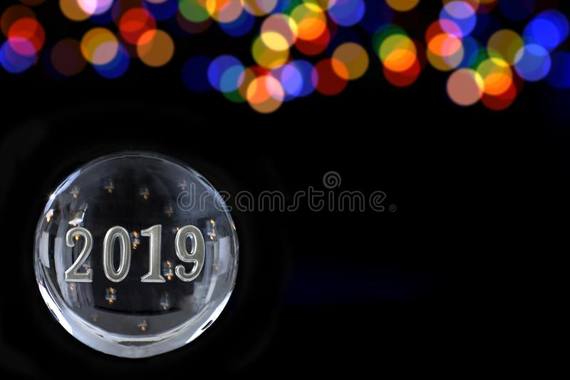 2019 em uma esfera mágica poderosa, no caixa de fortuna, no conceito do poder da mente no fundo preto com lbue e na luz obscura d imagens de stock