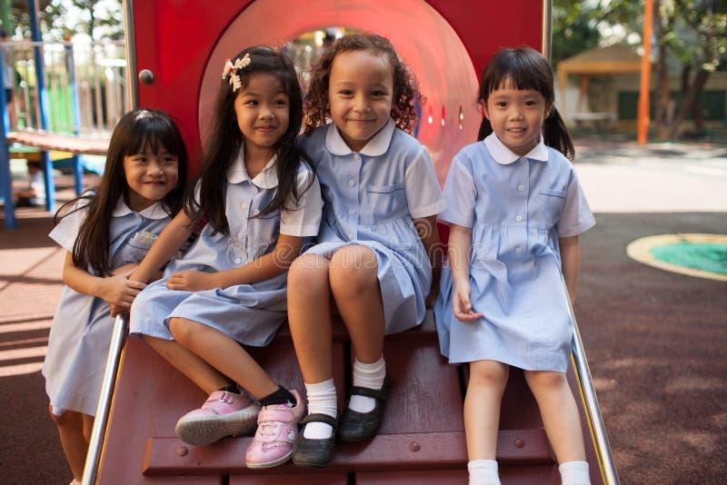 Em uma faculdade em Banguecoque, as crianças têm o divertimento no dur do campo de jogos imagem de stock royalty free