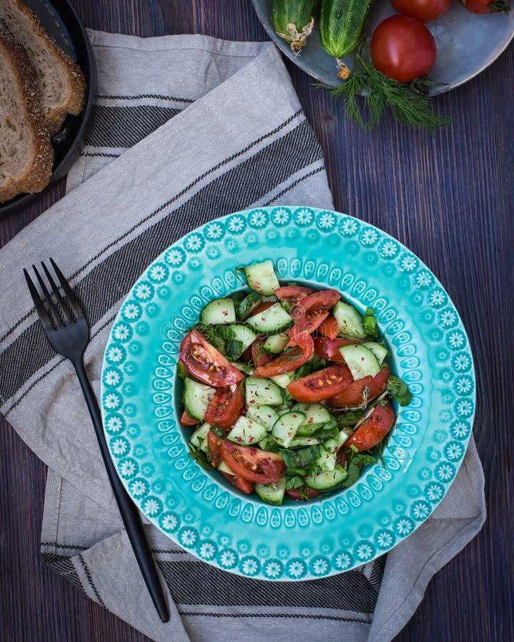 Em uma luz - placa azul uma salada de pepinos e de tomates frescos com verdes imagem de stock royalty free