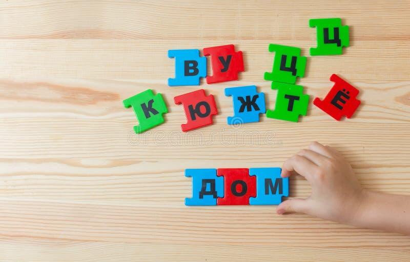 Em uma mentira de madeira do fundo as letras do alfabeto de russo Uma criança gasta a casa da palavra no russo imagens de stock
