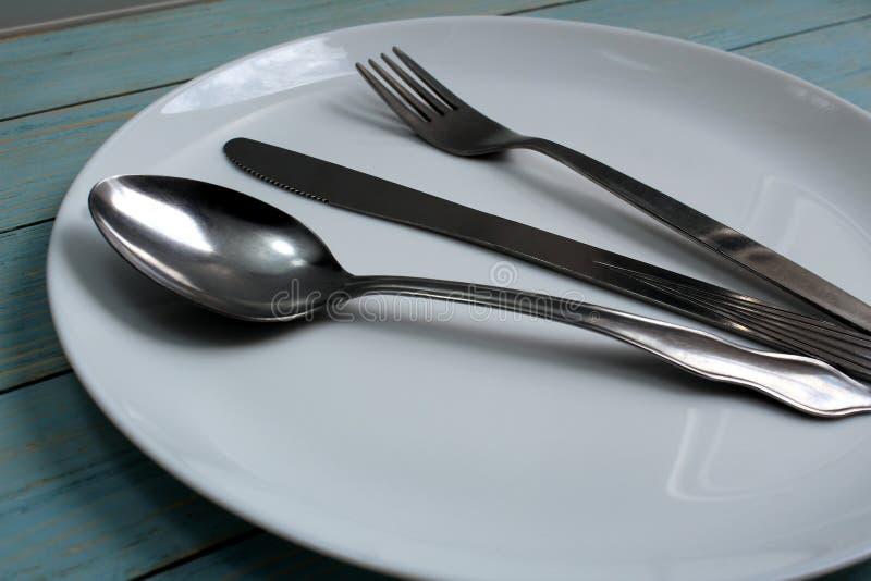 Em uma placa branca é a faca da cutelaria, forquilha, colher foto de stock