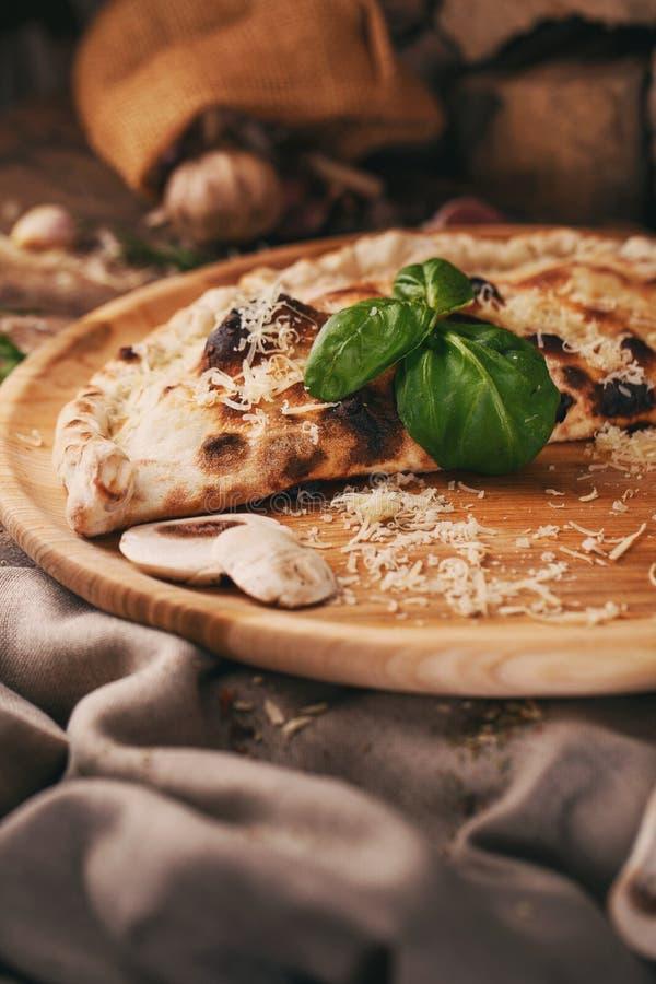 Em uma placa de madeira, em uma pizza Calzone, em uma manjericão, em uns cogumelos e em um queijo raspado imagens de stock royalty free