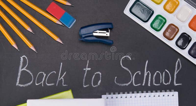Em uma placa preta, em uma inscrição do giz - outra vez à escola, e em torno de um grupo de lápis e de pinturas imagem de stock royalty free