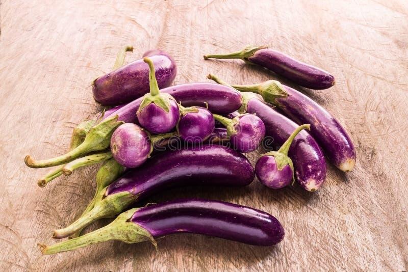 Em volta de e brinjal ou beringela ou beringela roxa crua orgânica fresca longa Beringelas roxas saudáveis e deliciosas na tabela fotos de stock royalty free