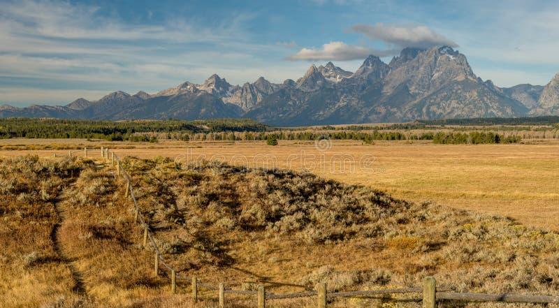 Em Wyoming a cordilheira de Teton com as cercas de um rood no fazendeiros coloca fotografia de stock