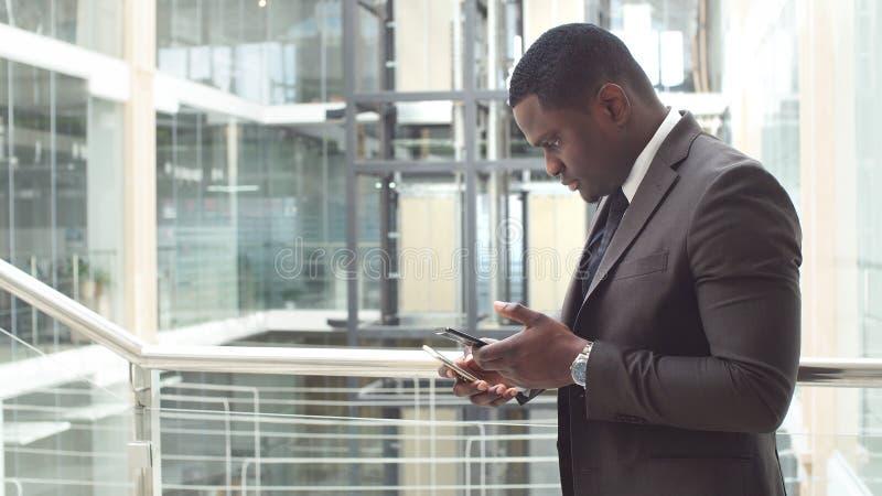 Email afroamericani della lettura dell'uomo d'affari sul suoi smartphone e risposte mandanti un sms fotografia stock