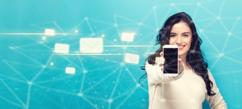 Email con la giovane donna che dà uno smartphone immagini stock