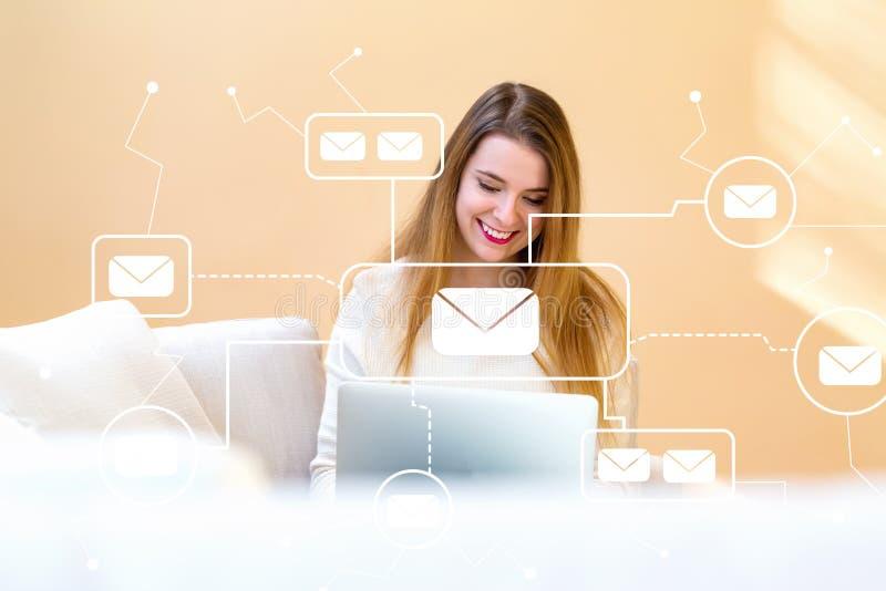 Email con la giovane donna che per mezzo del suo computer portatile fotografia stock libera da diritti