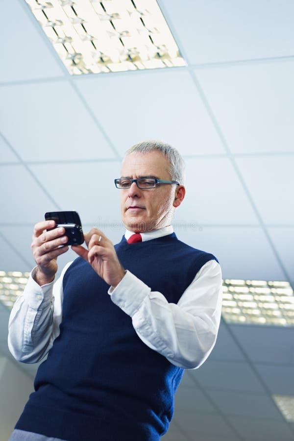 Email maduros de la lectura del hombre de negocios en el teléfono celular foto de archivo