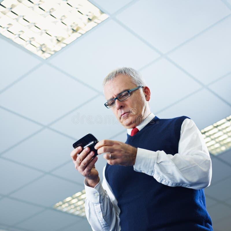 Email maduros de la lectura del hombre de negocios en el teléfono celular fotografía de archivo