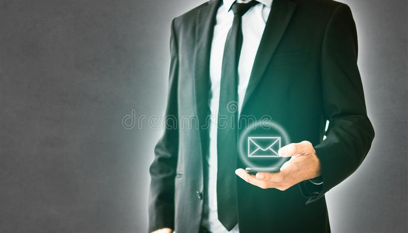 Email / mail symbol - man holds mobile phone, businessman using smartphone.  stock photography