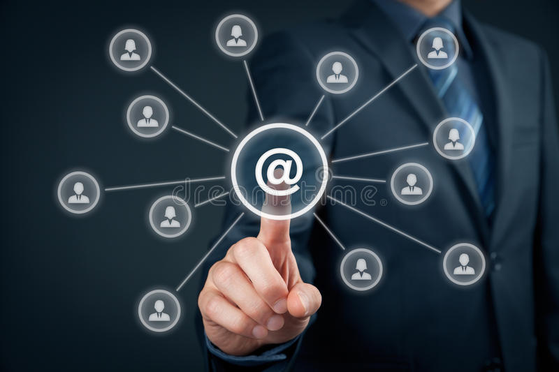 Email marketing and newsletter. Email marketing, newsletter and bulk mail concepts. Businessman click on button with at sign linked with people icons stock photography