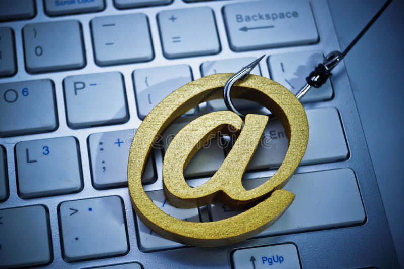 Email phishing attack. A fish hook with email sign on computer keyboard / Email phishing attack concept stock images