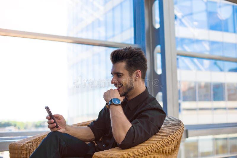 Email sonriente feliz de la lectura del hombre de negocios con buenas noticias en el teléfono móvil, sentándose en interior de la fotografía de archivo libre de regalías