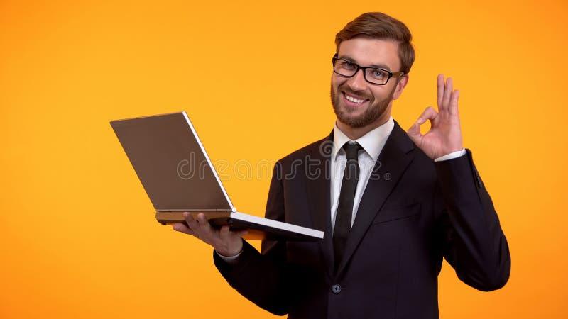 Email sonriente y mostrar de la lectura del hombre la muestra aceptable, gui?ando en la c?mara, promoci?n foto de archivo libre de regalías