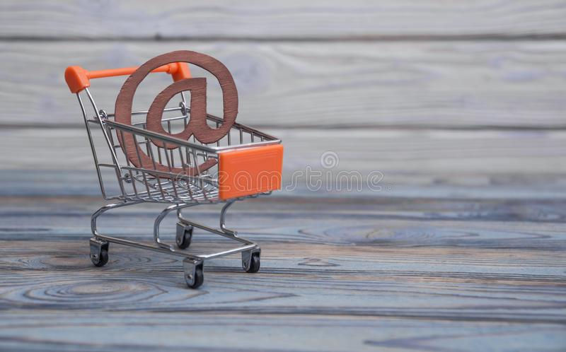 An email symbol, shopping cart. On a wood board background. The idea of buying online. depicting the concept of e-shopping or e-commerce stock images