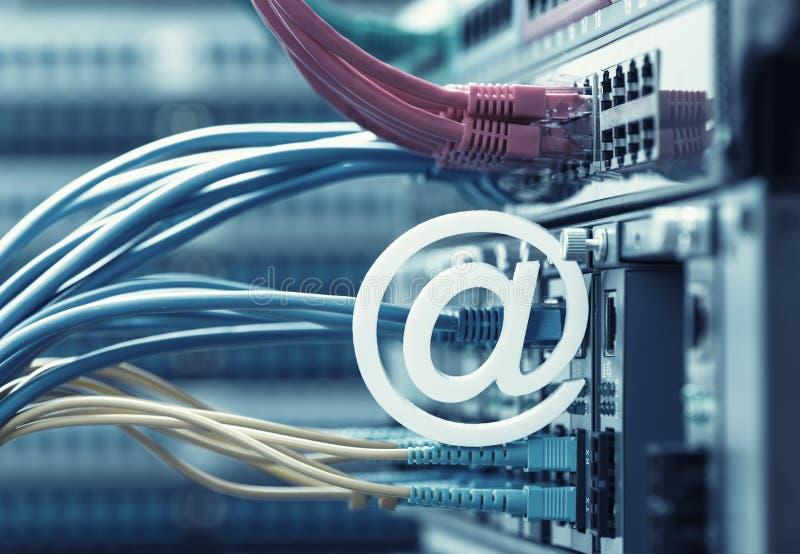 Email symbolet på nätverksströmbrytaren och Ethernetkablar royaltyfria foton