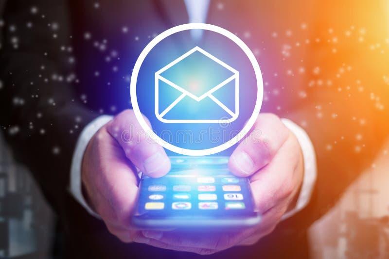 Emailsymbol som ut går en smartphonemanöverenhet av en affärsman - b royaltyfria bilder