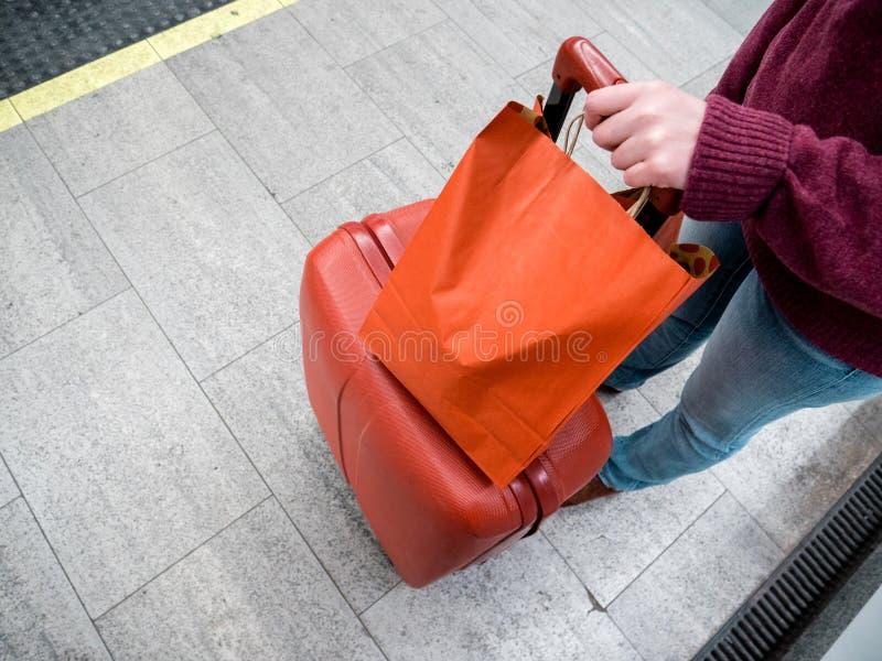 Emale妇女和拿着在平台火车的红色行李 库存照片
