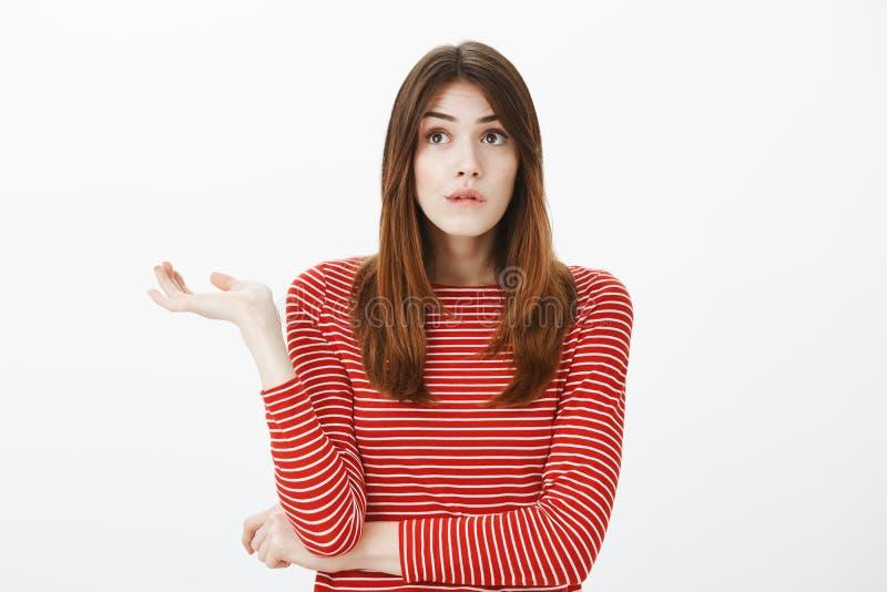 Emaranhado da menina nos pensamentos Retrato do estudante fêmea europeu incomodado à nora em blusa vermelha listrada, palma de es fotos de stock