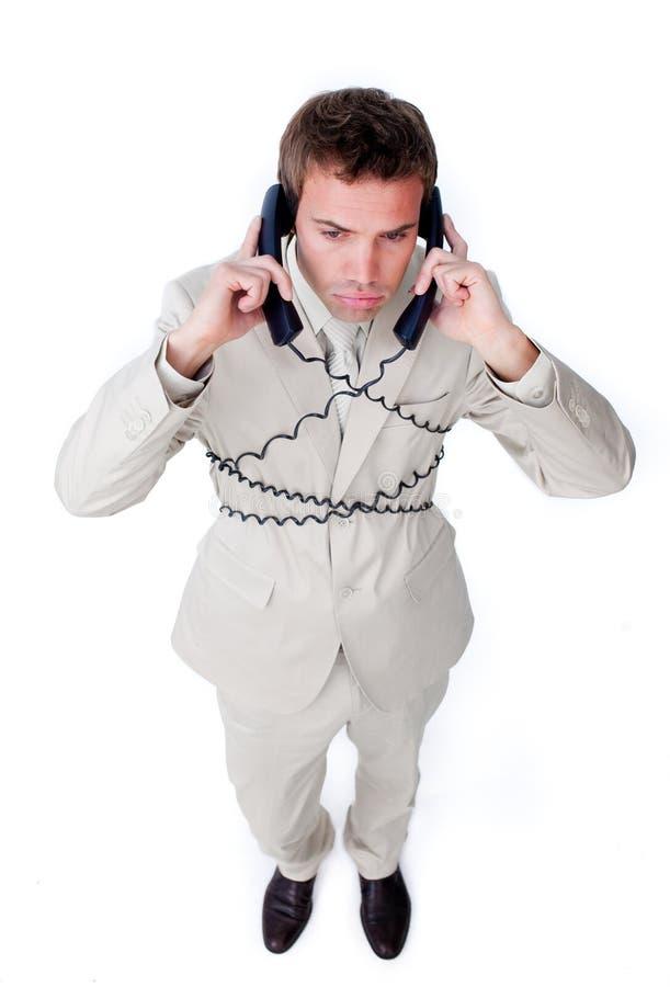 Emaranhado furado do homem de negócios acima em fios do telefone fotografia de stock royalty free