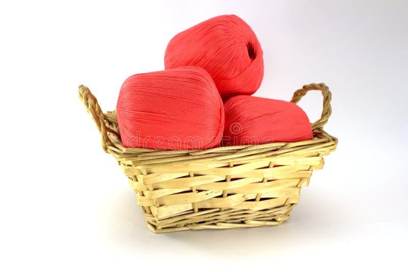 Emaranhados cor-de-rosa brilhantes do algodão natural para o bordado em uma cesta de vime em um fundo branco foto de stock