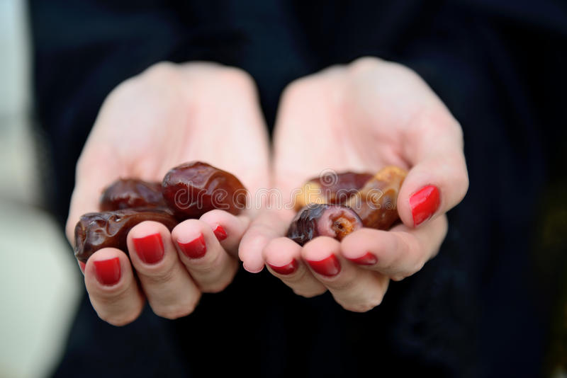 Emarati Arab woman holding dates in hand stock images