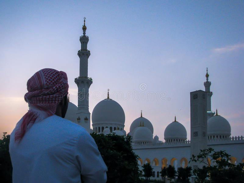 Emarati man looking at Sheikh Zayed Grand mosque stock photography