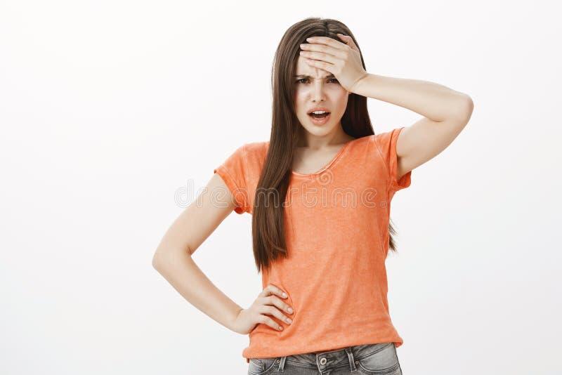 Embêtement énorme sur la tête de femme Portrait de la fille européenne déçue contrariée, fâché et intense, tenant la main sur le  photo libre de droits