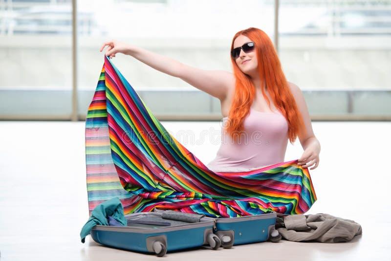 A embalagem da jovem mulher para férias do curso fotos de stock