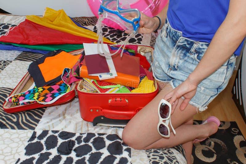 Embalagem da mulher que prepara-se para férias de verão Mala de viagem da embalagem da moça na cama em casa fotos de stock