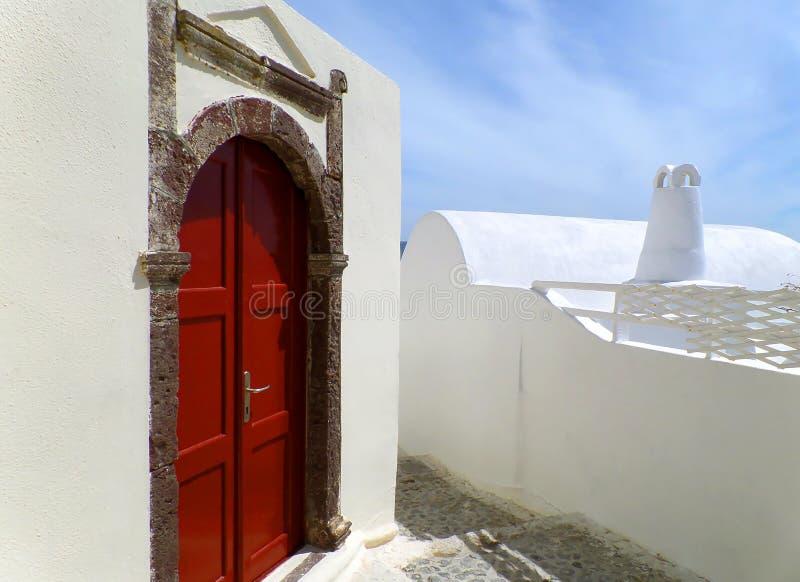 Embalagem de porta grega impressionante do estilo com profundamente - a porta vermelha na construção branca pura em Santorini fotos de stock royalty free