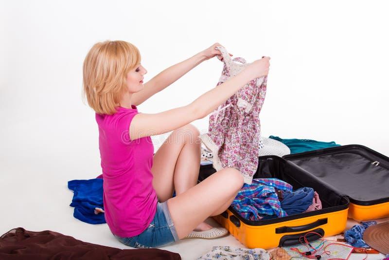 Embalaje bastante femenino de los jóvenes su maleta antes fotos de archivo libres de regalías