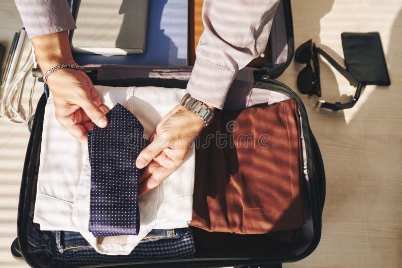 Embalaje del hombre de negocios para el viaje foto de archivo