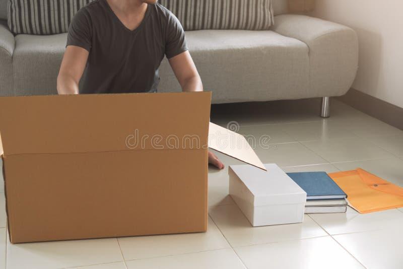 Embalaje del hombre y materia asiáticos jovenes el poner en la caja de cartón grande f foto de archivo libre de regalías