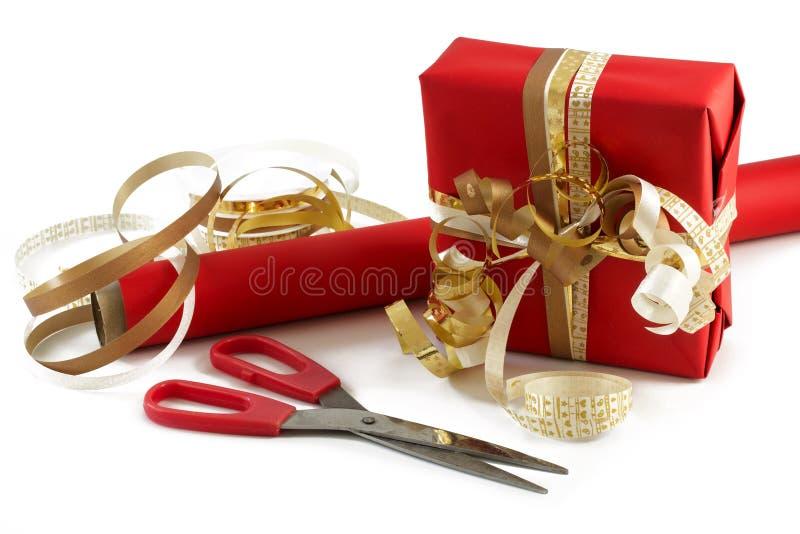 Emballage d'un présent avec les ciseaux, le papier rouge et les rubans d'or f images libres de droits