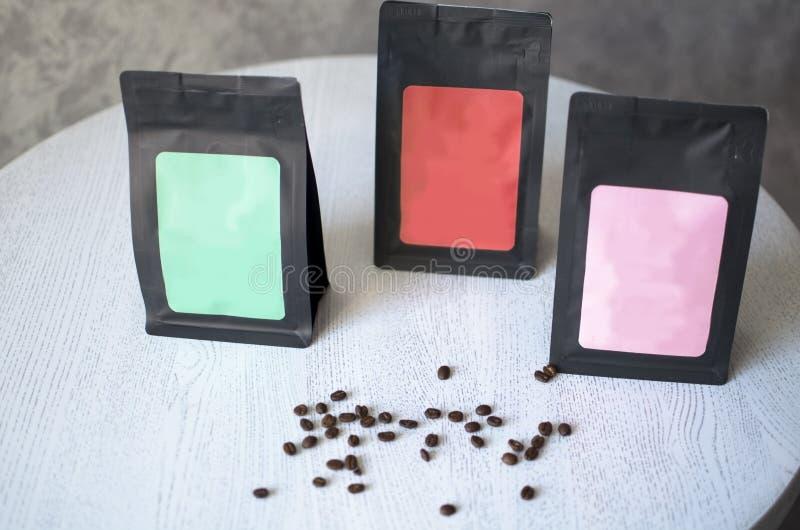Emballage för svart kaffe med klistermärken står på den vita tabellen spiffied royaltyfri foto