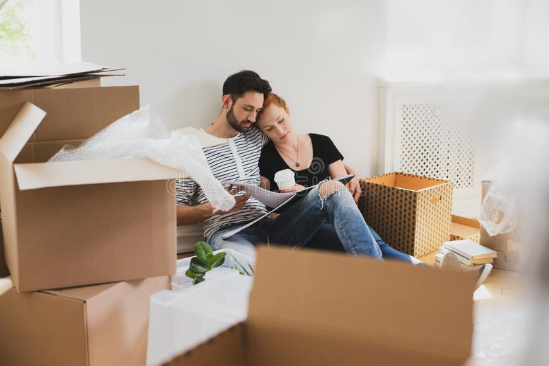 Emballagematerial för den lyckliga förbindelsen in i lådan boxas medan flyttningen-ut arkivfoton
