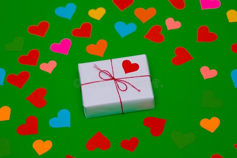 Emballerad gåvaask på en grön bakgrund med många mångfärgade hjärtor omkring arkivbilder