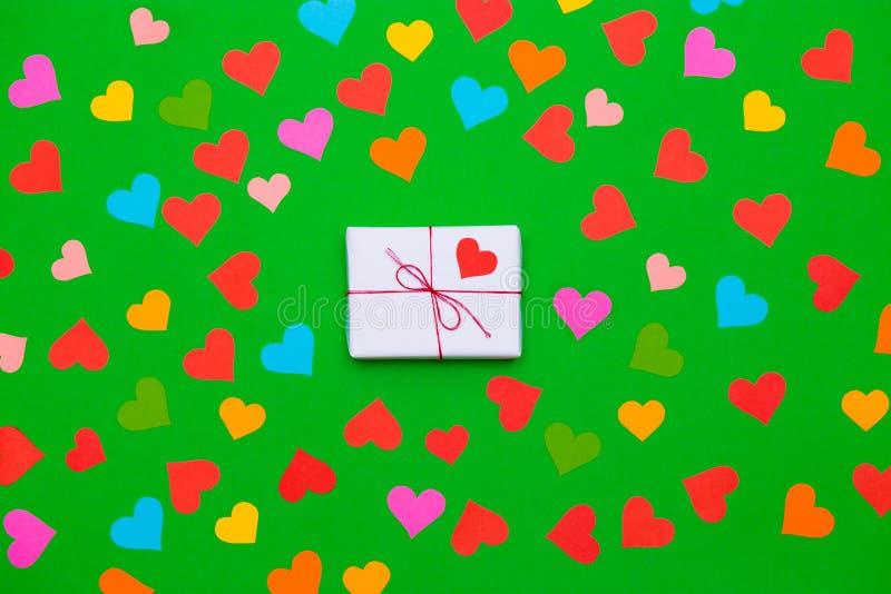 Emballerad gåvaask på en grön bakgrund med många mångfärgade hjärtor omkring royaltyfri bild