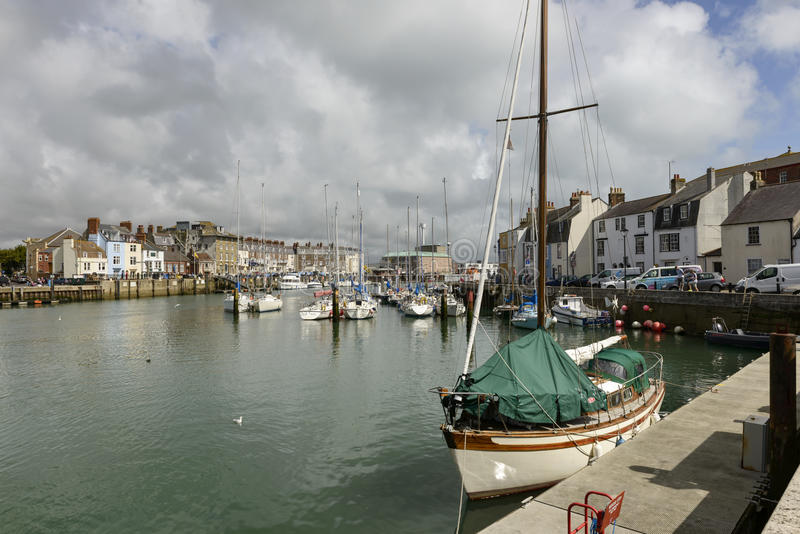 Embankements in canal harbour, Weymouth. WEYMOUTH, UNITED KINGDOM - AUGUST 26, many boats moored in the canal harbour of touristic historic village of Somerset stock photography