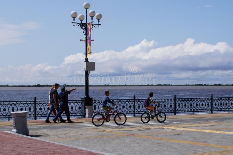 Embankment of Amur River. On summer day, people walk along sidewalk. Local man in uniform shows young couple of stock photography