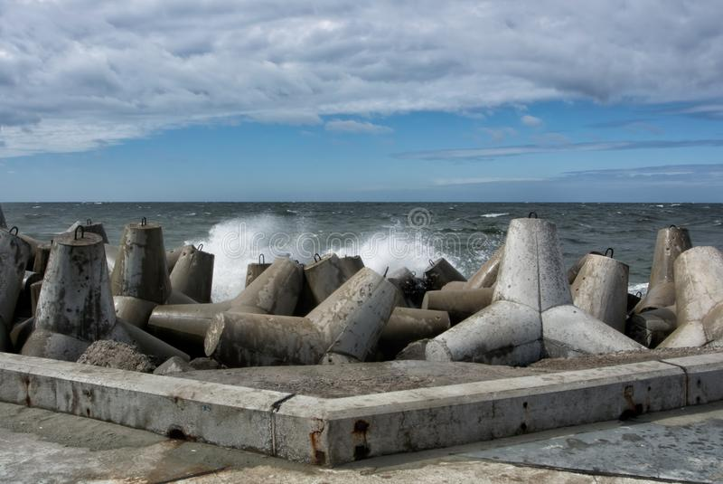 An embankment of Baltic sea at the city Baltiysk on cloudy summer day, a view to the gray seascape, waves and big stone blocks royalty free stock images