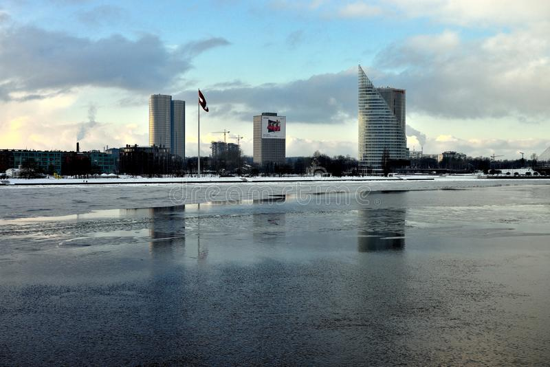 Embankment of the Western Dvina. Riga. Latvia. Embankment of the Western Dvina. The river is covered with a thin crust of ice. Three skyscrapers in the stock image