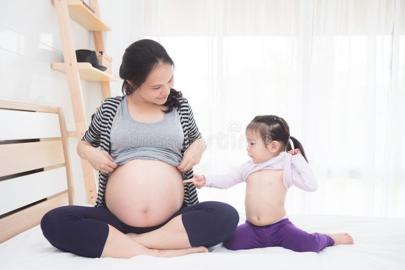 Embarazada y su hija que muestran su vientre en cama foto de archivo