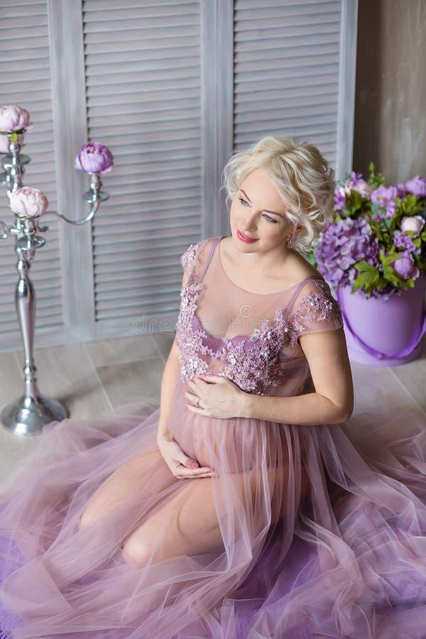 Embarazo, maternidad y concepto futuro feliz de la madre - mujer embarazada en vestido violeta airoso con las flores del ramo con fotografía de archivo libre de regalías