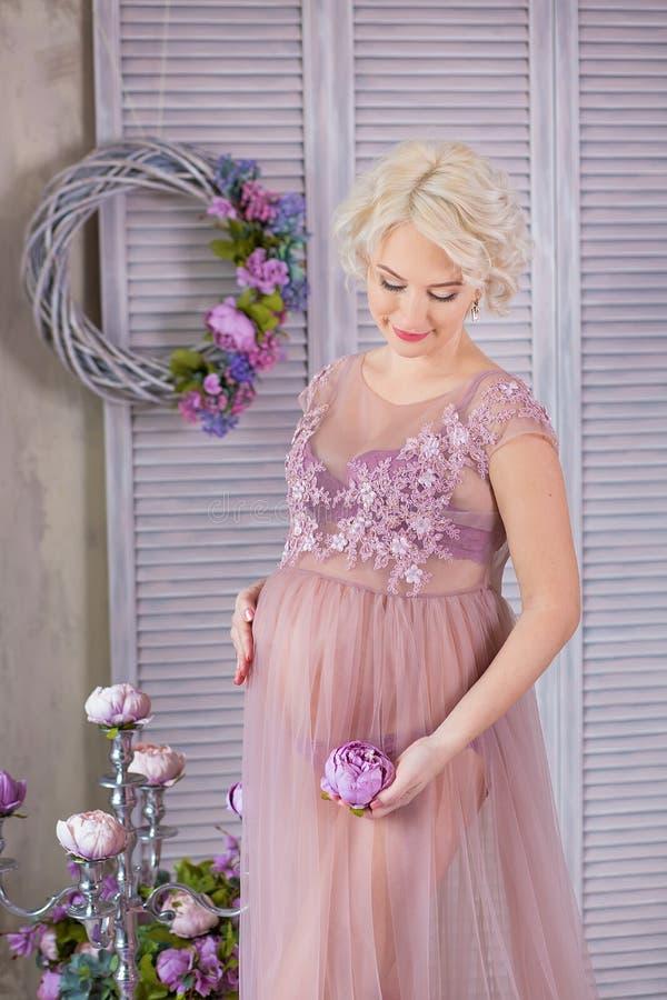 Embarazo, maternidad y concepto futuro feliz de la madre - mujer embarazada en vestido violeta airoso con las flores del ramo con imagen de archivo libre de regalías