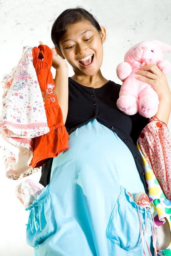 Embarazo y compras de la ropa del bebé imagenes de archivo