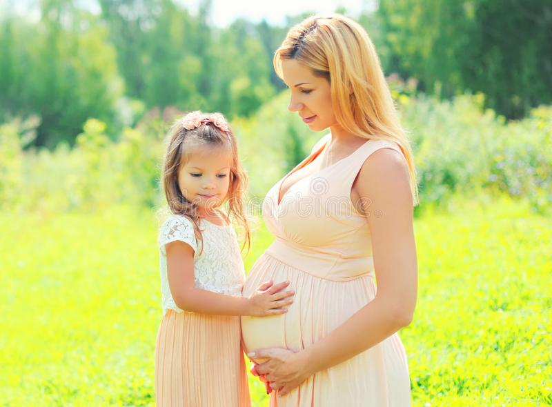 Embarazo y concepto de familia - la mujer embarazada feliz, hija del pequeño niño toca a la madre del vientre en verano fotografía de archivo